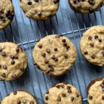 These are healthy banana chocolate chip muffins. The is a wire cooling rack filled with golden muffins topped with several melted mini chocolate chips. There are 12 muffins lined up on the wire cooling rack.