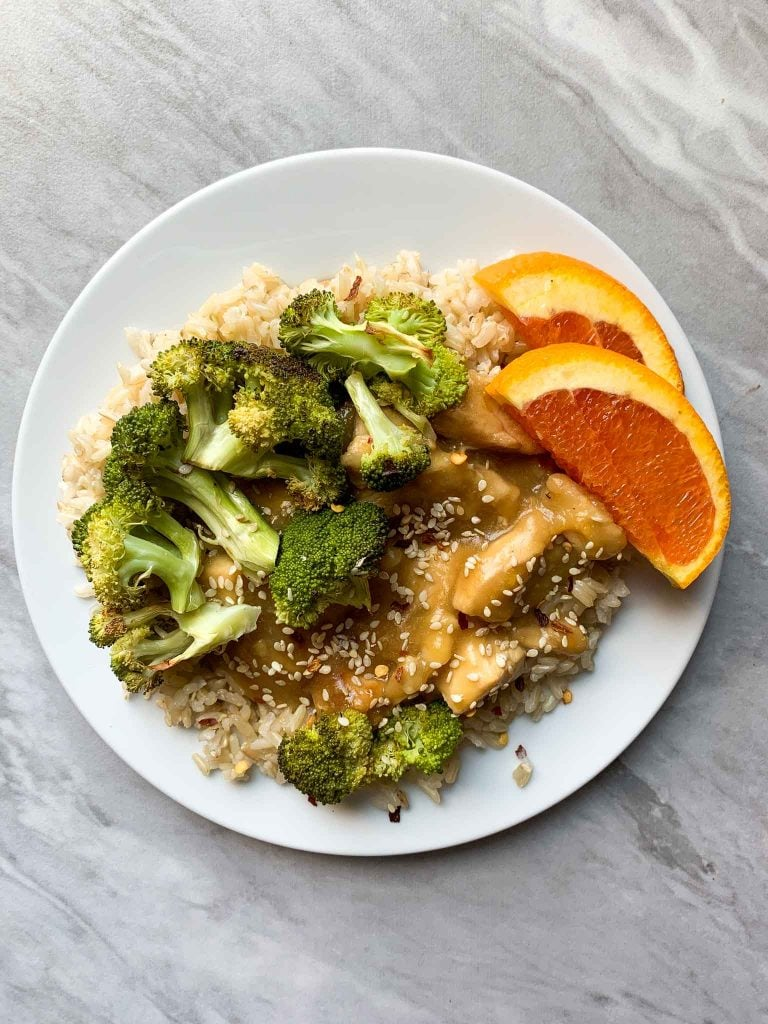 This is a plate for healthy orange chicken. The plate is filled with brown rice topped with orange chicken, broccoli, and orange slices.