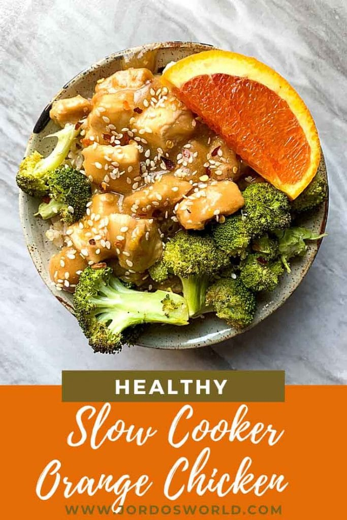 This is a pinterest pin for healthy orange chicken that is made in a slow cooker. There is a bowl filled with brown rice and topped with broccoli, orange chicken, and orange slices.