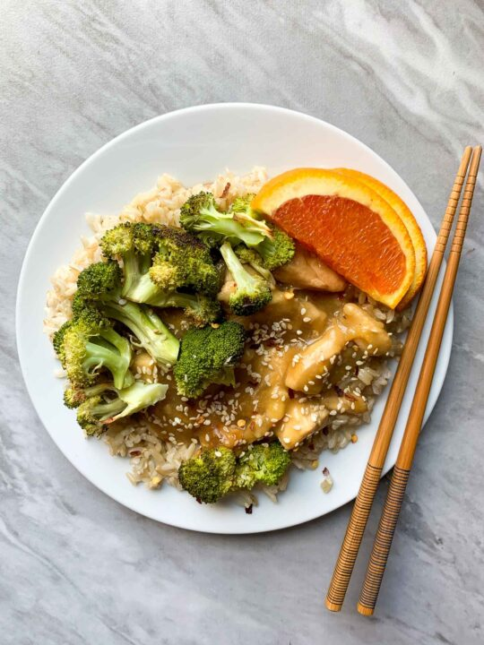 This is a plate for healthy orange chicken. The plate is filled with brown rice topped with orange chicken, broccoli, and orange slices. There is a pair of chopsticks on the side of the plate as well.