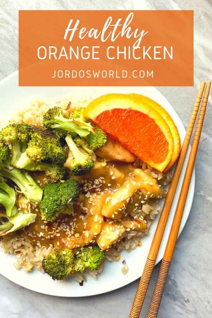 This is a pinterest pin for healthy orange chicken that is made in a slow cooker. There is a plate covered in brown rice and topped with broccoli, orange chicken, and oranges. There is a pair of chopsticks on the plate as well.