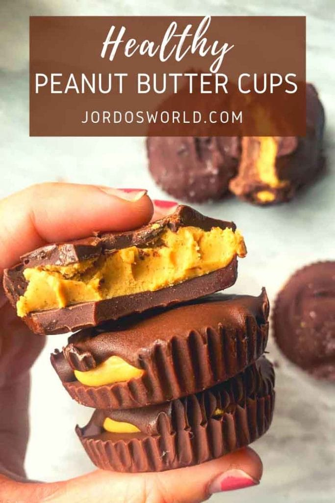 These are healthy peanut butter cups. There is a hand holding up 3 cups stacked on top of each other, the top one with a bite out of it. There are large chocolate cups in the background as well.These are healthy peanut butter cups. There is a hand holding up 3 cups stacked on top of each other, the top one with a bite out of it. There are large chocolate cups in the background as well.
