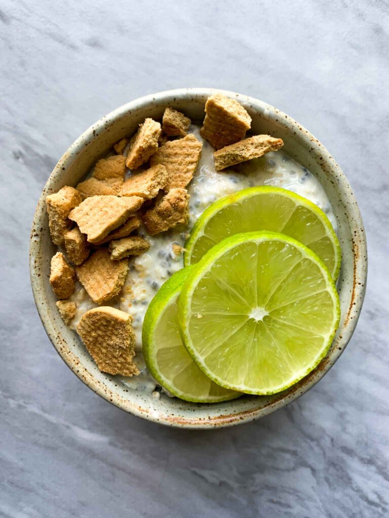 This is a bowl of key lime pie overnight oats. There are the oats topped with graham pieces and limes.