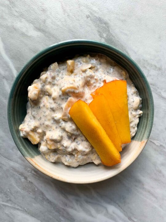 This is a bowl filled with peach cobbler overnight oats. There are oats with all of the ingredients mixed in and it is topped with sliced peaches.