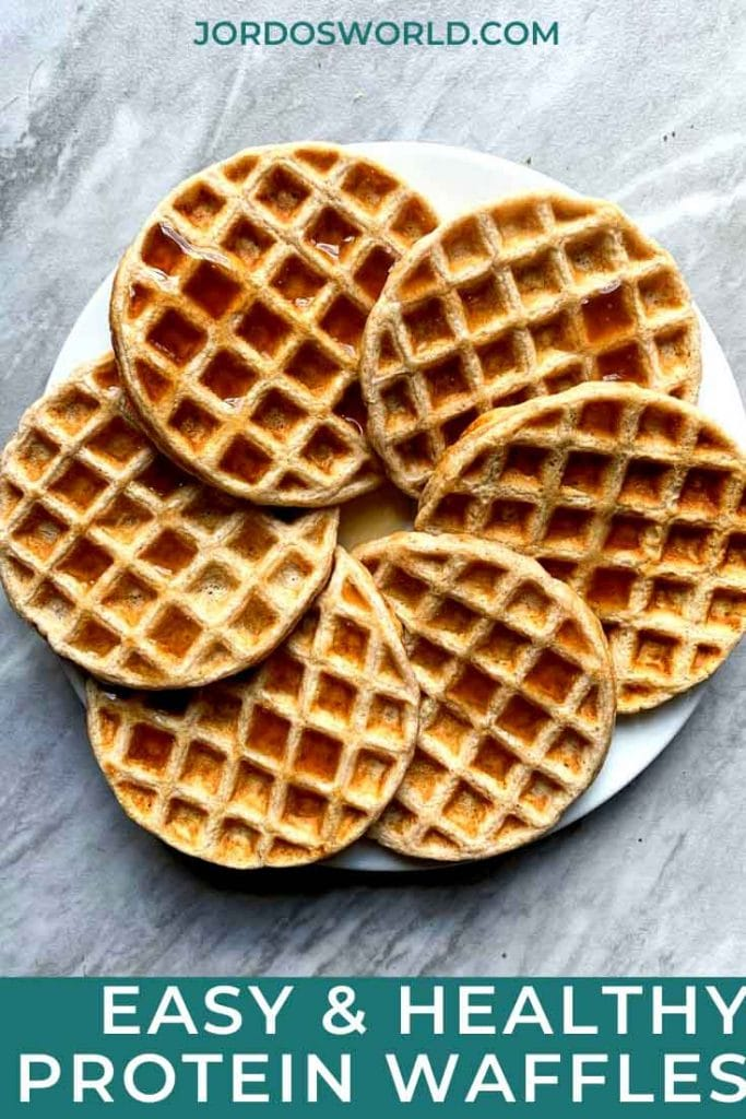 This is a pinterest pin for protein waffles. There is a plate filled with crispy, warm protein waffles. There is maple syrup on top as well.