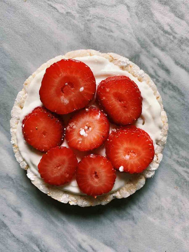 This is a rice cake topped with white vanilla greek yogurt, sliced strawberries, and powdered sugar.