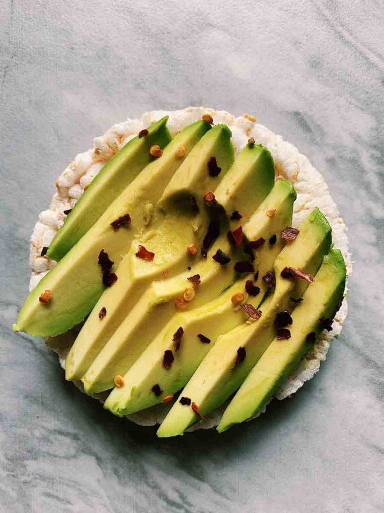 This is a rice cake topped with sliced avocado and red pepper flakes.