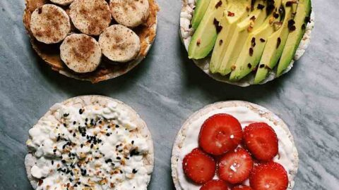 These are four rice cake snacks, each topped a different way. One is peanut butter and banana, another is sliced avocado, another is cottage cheese and seasoning, and the last is berries and yogurt.