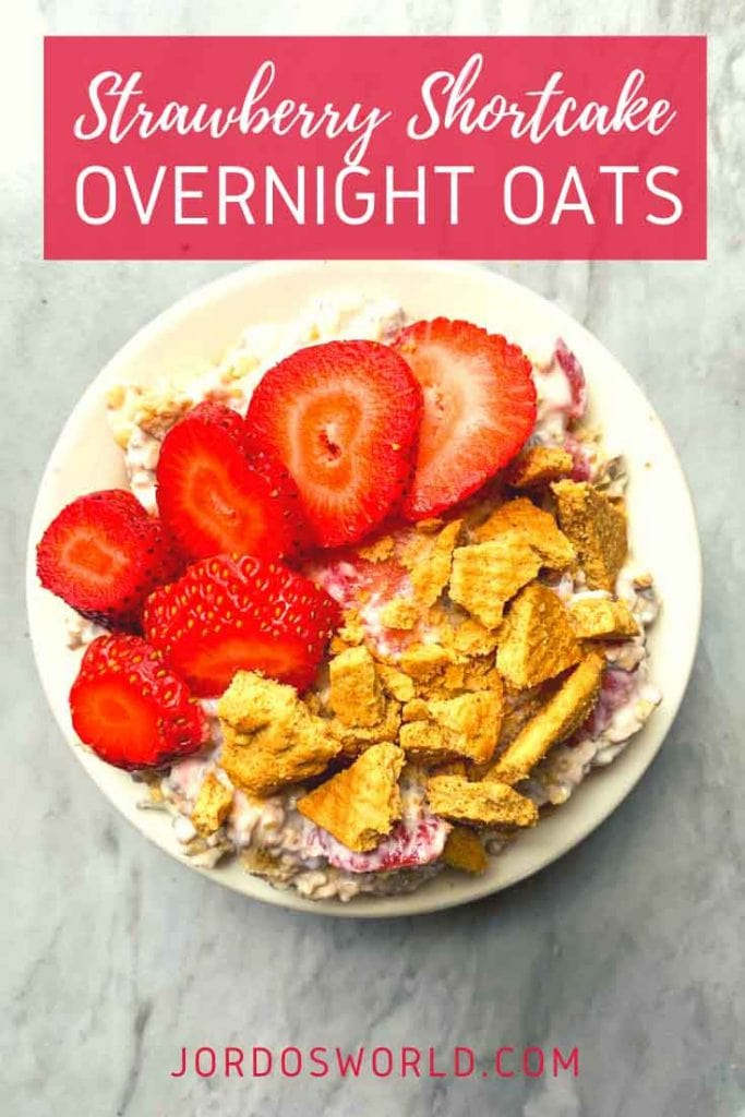 This is a bowl filled with strawberry shortcake overnight oats. There is a bowl of oats topped with sliced strawberries and crushed graham crackers.