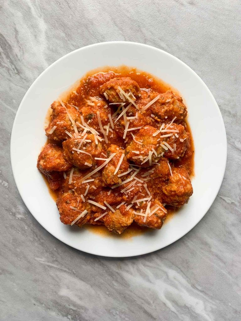 This is a plate of turkey meatballs. The meatballs are covered in sauce and topped with parmesan cheese.