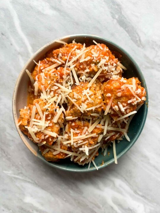 This is a bowl of turkey meatballs. The meatballs are covered in sauce and topped with parmesan cheese.
