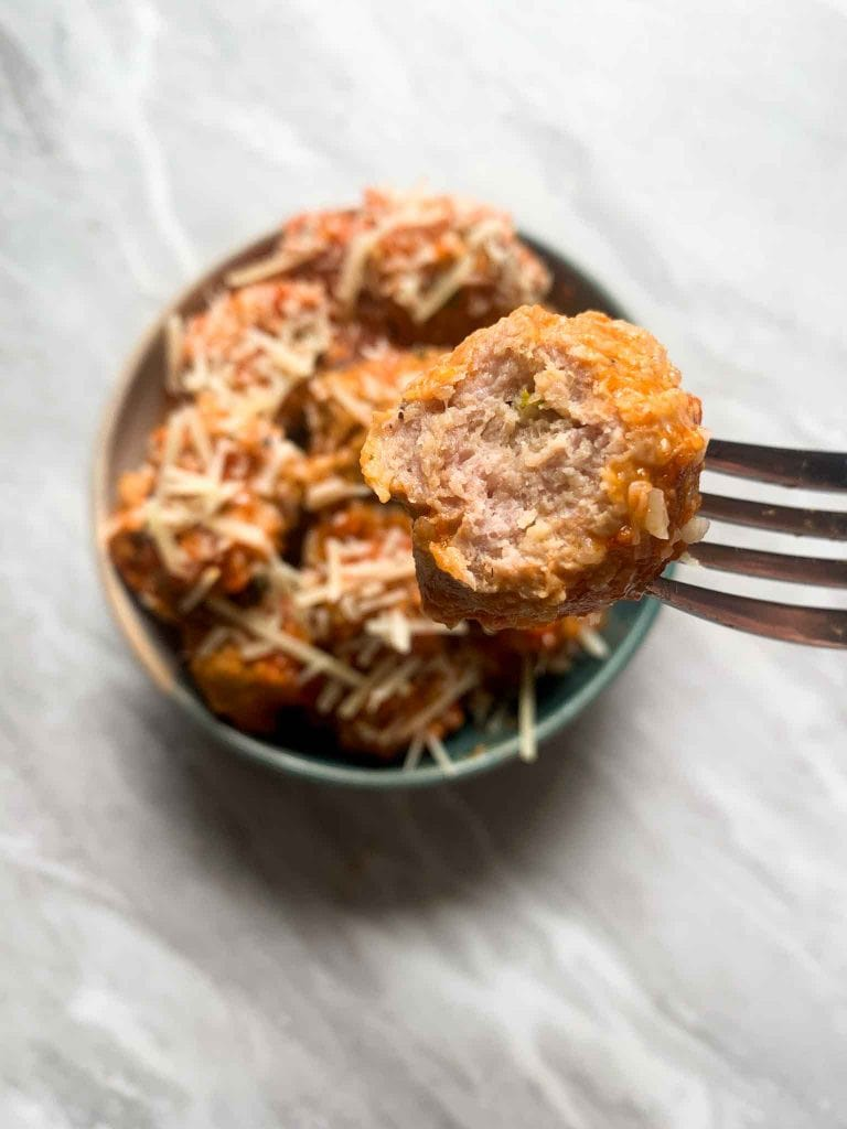 There is a bowl of turkey meatballs. The meatballs are covered in sauce and topped with parmesan cheese. There is a fork holding up a meatball with a bite into it.
