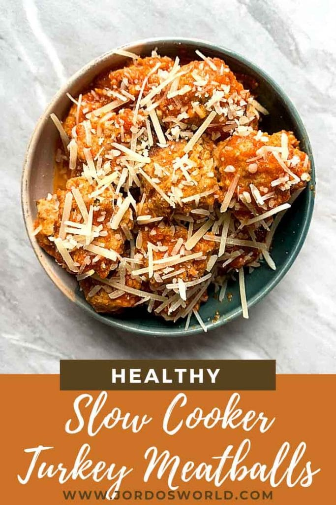 This is a pinterest pin for turkey meatballs. There is a bowl filled with the turkey meatballs covered in sauce and cheese.