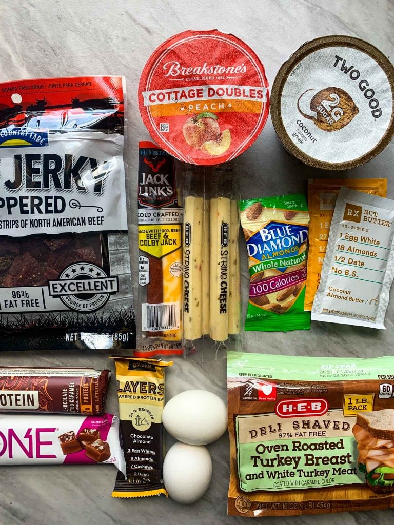 This is an assortment of high-protein, low-carb snacks. There is greek yogurt, cottage cheese, jerky, cheese sticks, nuts, nut butter, bars, eggs, and turkey.