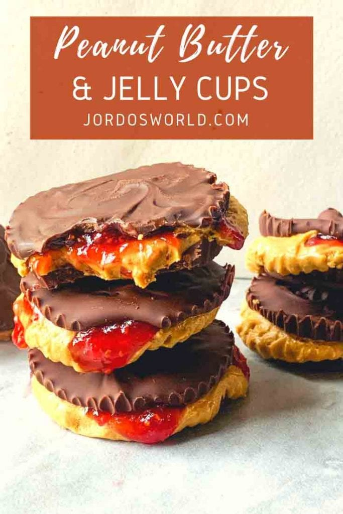 This is a pinterest pin for peanut butter and jelly cups. These peanut butter and jelly cups have two layers of chocolate with peanut butter and jelly sandwiched in between. There is a stack of the peanut butter & jelly cups with the insides oozing out so you can see the layers of peanut butter & jelly.