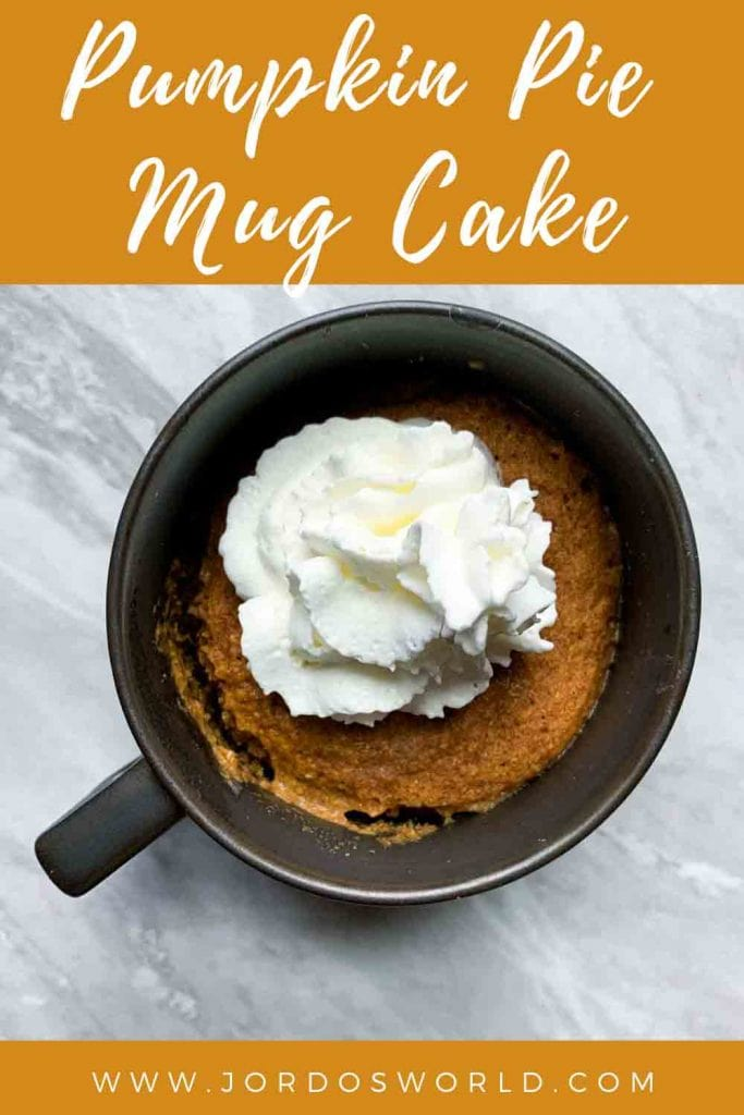 This is a pinterest pin for the pumpkin mug cake. There is a small ceramic mug with a pumpkin mug cake on the inside, topped with whipped cream.