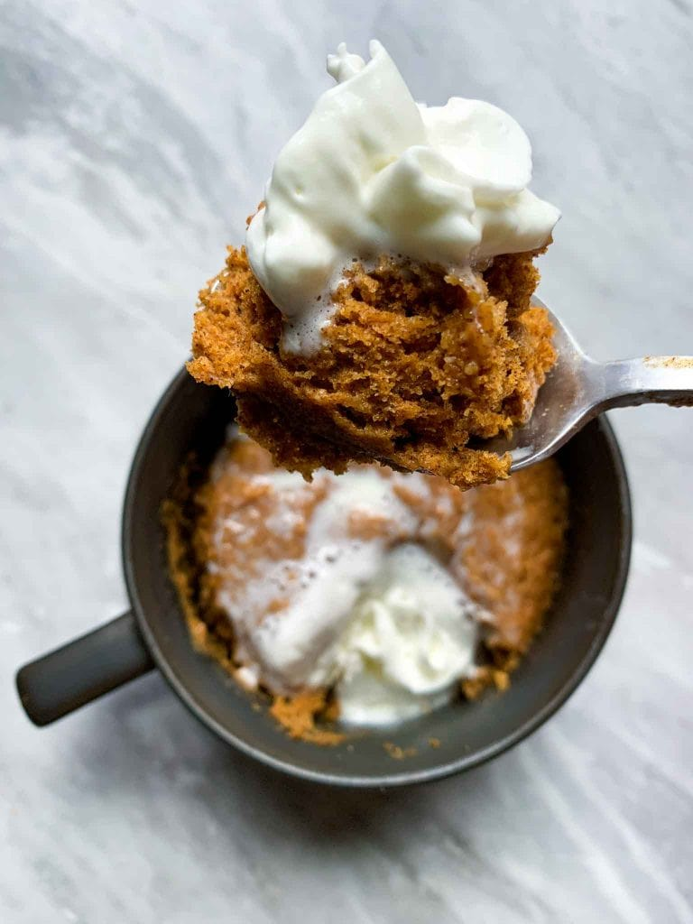 This is a pumpkin mug cake. There is a small coffee mug filled with pumpkin cake and topped with a dollop of whipped cream. There is a spoonful of mug cake with whipped cream held up in the air.