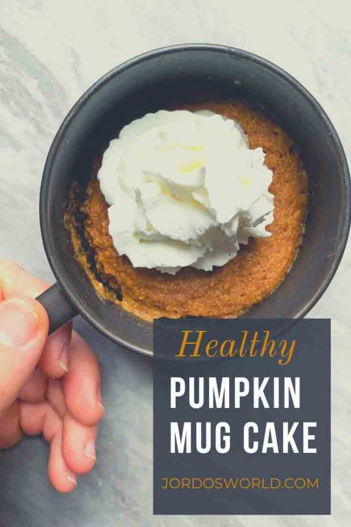 This is a pinterest pin for the pumpkin mug cake. There is a small ceramic mug with a pumpkin mug cake on the inside, topped with whipped cream. There is a hand holding the mug as well.