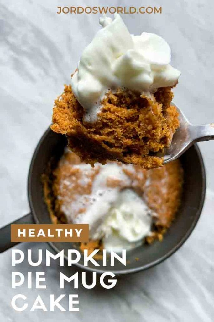 This is a pinterest pin for the pumpkin mug cake. There is a small ceramic mug with a pumpkin mug cake on the inside, topped with whipped cream. There is a spoonful of the pumpkin mug cake with whipped cream on top as well.