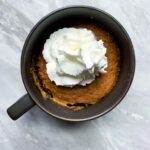 This is a pumpkin mug cake. There is a small coffee mug filled with pumpkin cake and topped with a dollop of whipped cream.