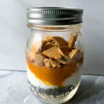 This is a mason jar filled with pumpkin pie overnight oats. There are layers of all of the ingredients -- oats, chia seeds, greek yogurt, pumpkin, vanilla, spices, and bear bites.