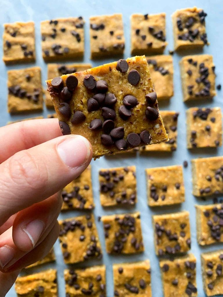 These are pumpkin protein bars. There is a marble slab filled with pumpkin protein squares cut into squares. Each square is orange pumpkin topped with chocolate chips. There is a hand holding up a close up of one of the bars as well.