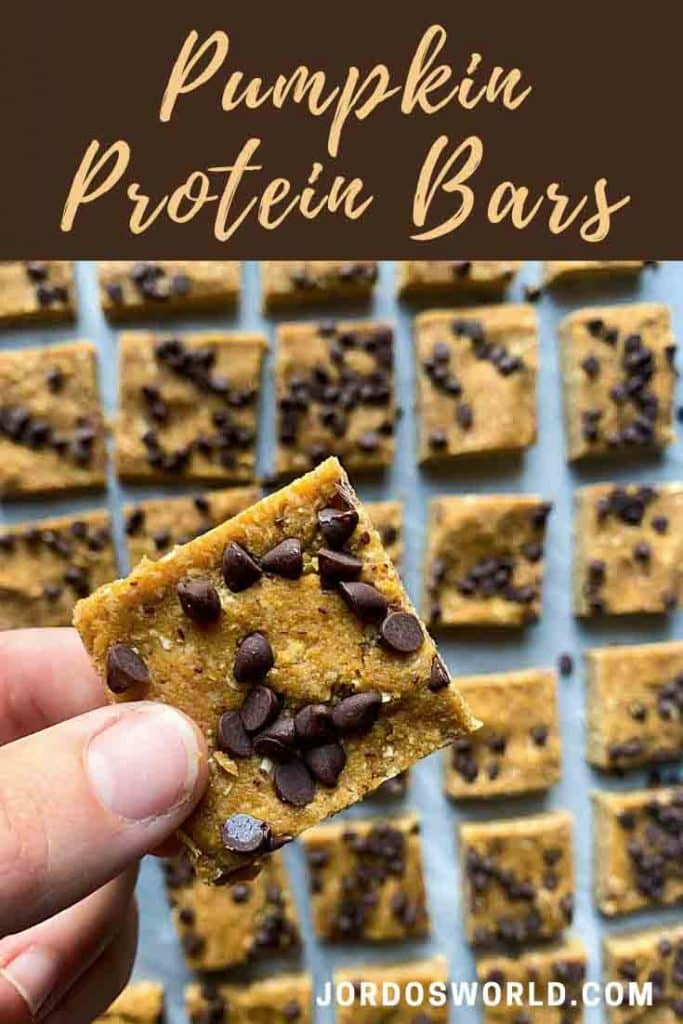 This is a pinterest pin for pumpkin protein bars. There is a hand holding up a bar with rows of square pumpkin and chocolate protein bars on a marble plate.