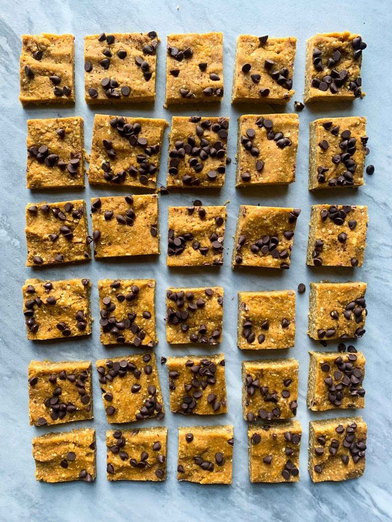 These are pumpkin protein bars. There is a marble slab filled with pumpkin protein squares cut into squares. Each square is orange pumpkin topped with chocolate chips.