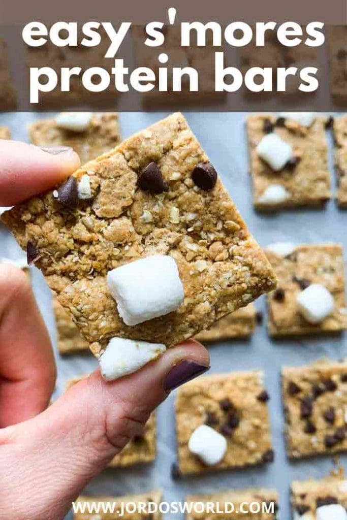 This is a pinterest pin for s'mores protein bars. There is a hand holding up a protein bar topped with marshmallows, graham crackers, and mini chocolate chips.