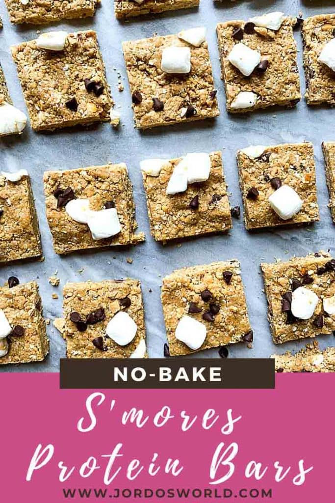 This is a pinterest pin for s'mores protein bars. There are rows of protein bars topped with marshmallows, graham crackers, and mini chocolate chips.