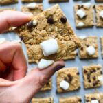 These are s'mores protein bars. There are several rows of bars cut into squares. Each square is topped with mini marshmallows, mini chocolate chips, and smashed graham crackers. A hand is holding up one of these bars so you can see the close up view.