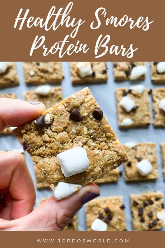 This is a pinterest pin for s'mores protein bars. There are rows of protein bars topped with marshmallows, graham crackers, and mini chocolate chips. There is a hand holding up one of the protein bars as well.