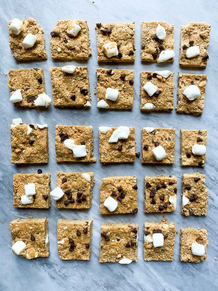 These are s'mores protein bars. There are several rows of bars cut into squares. Each square is topped with mini marshmallows, mini chocolate chips, and smashed graham crackers.