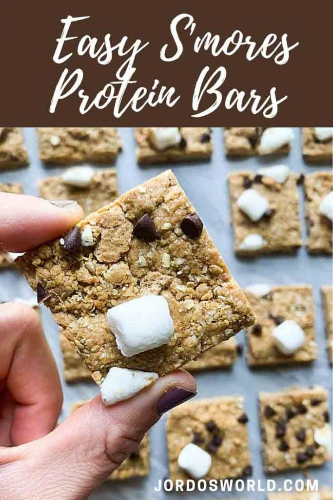 This is a pinterest pin for s'mores protein bars. There are rows of protein bars topped with marshmallows, graham crackers, and mini chocolate chips. There is a hand holding up a protein bar as well.