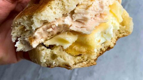 This is a copy cat chick-fil-a egg white grill. There is a hand holding a breakfast sandwich with a bite out of it. The sandwich has an english muffin, cheese, egg white patty, and chicken breast.