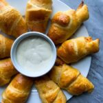 These are buffalo chicken rolls. There are crescent rolls wrapped up with buffalo chicken on the side. The crescent rolls are formed in a star shape on a plate with a bowl of ranch dipping sauce in the middle.
