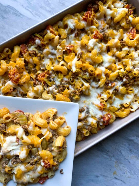 This is a picture of cheeseburger casserole. There are elbow macaroni noodles covered in cheese, hamburger, pickles, tomatoes, and other cheeseburger ingredients. There is a big dish of the casserole and a smaller plate with a scoop on it.