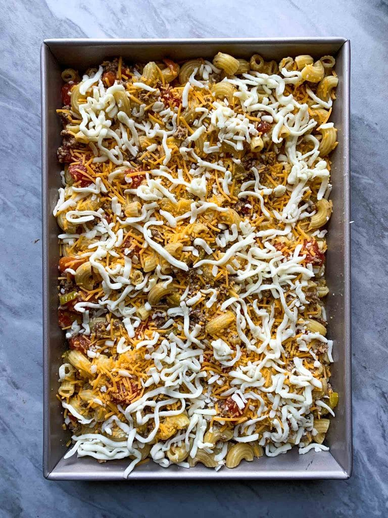 This is a picture of cheeseburger casserole. There are elbow macaroni noodles covered in cheese, hamburger, pickles, tomatoes, and other cheeseburger ingredients. This is the casserole pre-baked.
