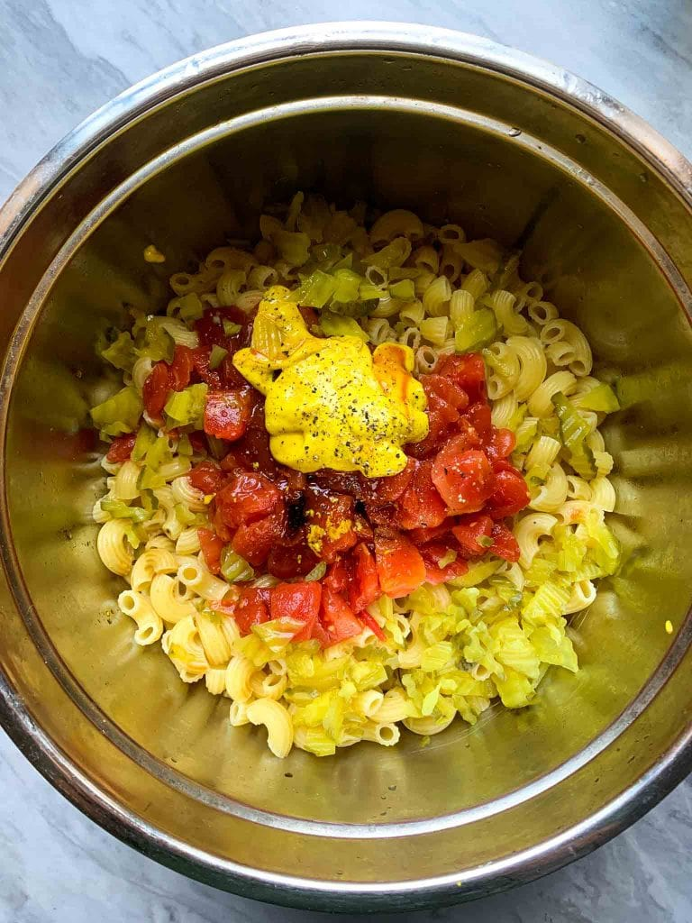 This is all of the ingredients for the casserole. The ingredients are in a large bowl. You can see noodles, tomatoes, mustard, pickles, and some seasonings.