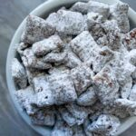 This is chex mix puppy chow. There is chex cereal coated with peanut butter and chocolate, along with white powdered sugar.