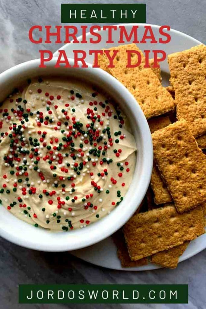 This is a pinterest pin for a healthy christmas party dip. There is a gingerbread dip topped with red and green spinkles, and graham crackers on the side.