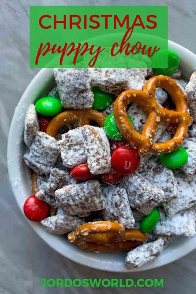 This is a pinterest pin for christmas puppy chow. There is chex cereal coated in a chocolate peanut butter mixture and white powdered sugar. There is also red and green m&m candies and pretzels mixed in.
