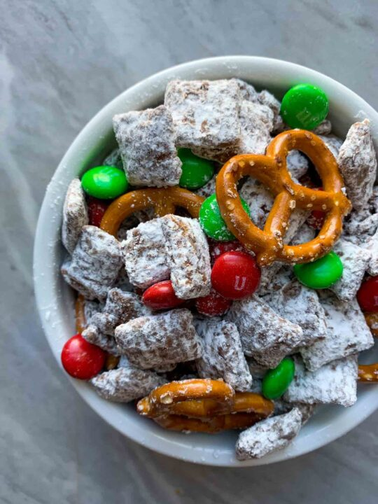 This is christmas puppy chow. There is chex cereal coated in a chocolate peanut butter mixture and white powdered sugar. There is also red and green m&m candies and pretzels mixed in.
