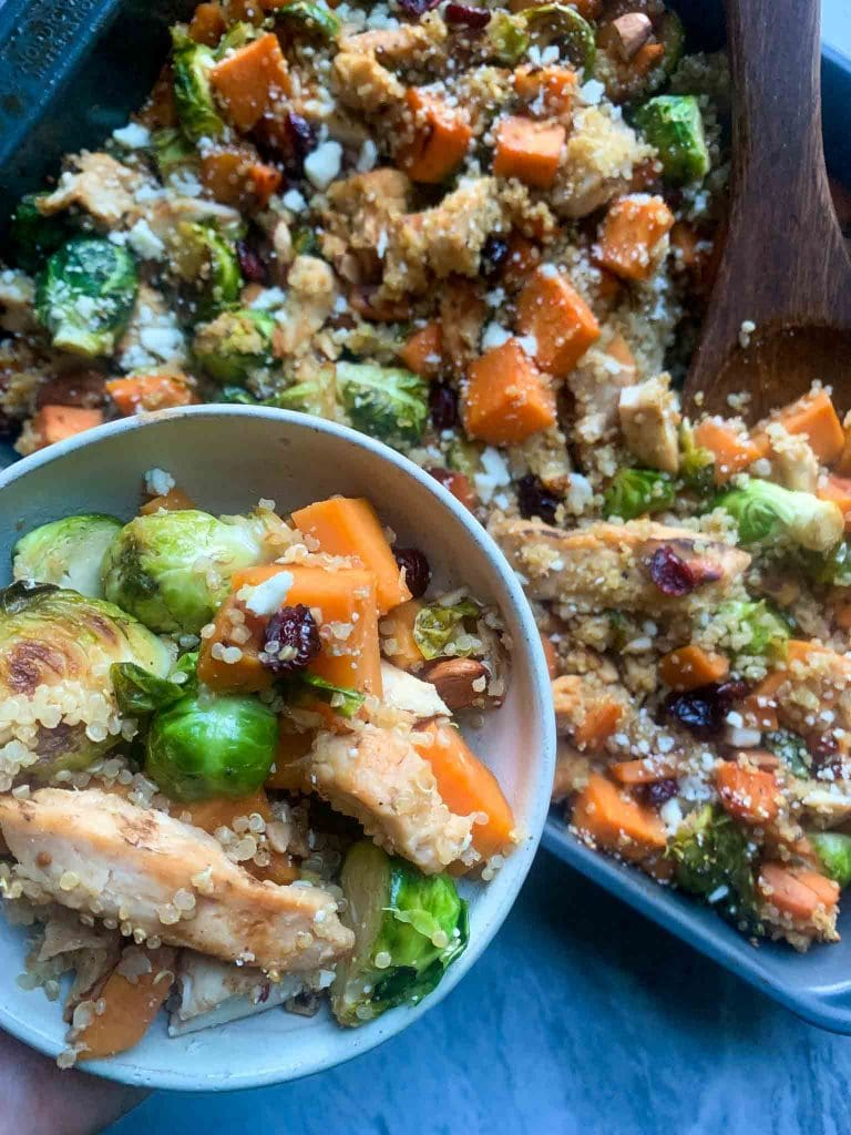 This is harvest chicken casserole. There is a large casserole dish filled with quinoa, chicken, sweet potato cubes, brussel sprouts, cranberries, almonds, and feta cheese. There is a large wooden spoon in the dish, ready to scoop out a serving of the dish. There is also a small bowl with a serving of this so you can see a close-up of all the ingredients.