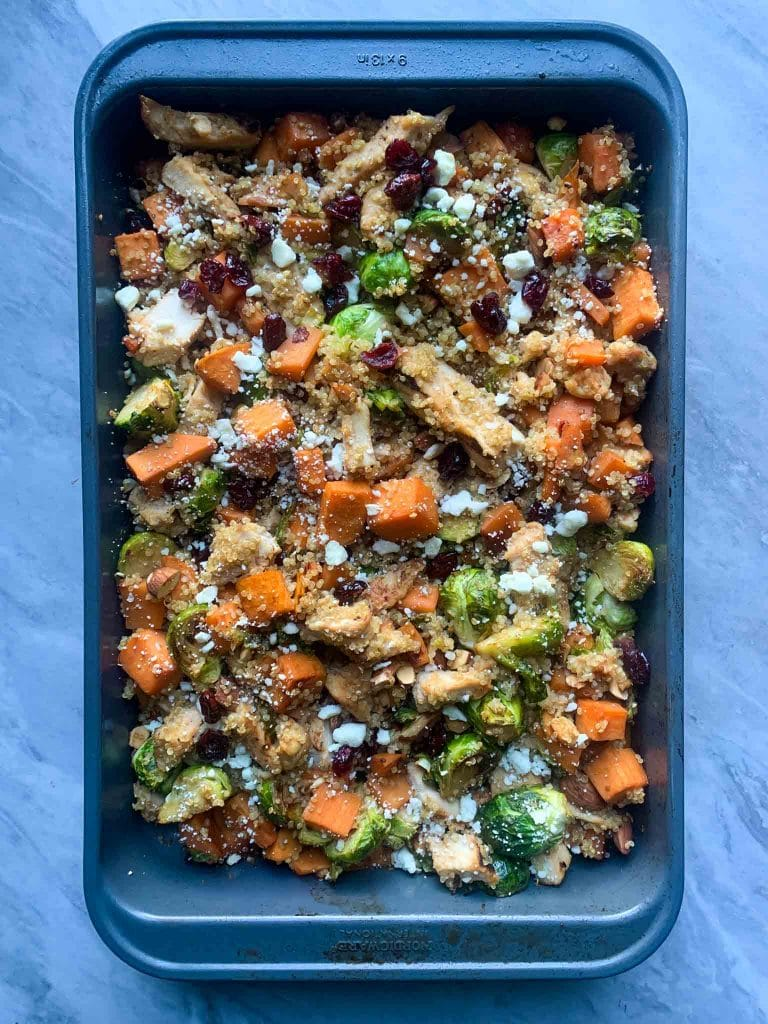 This is harvest chicken casserole. There is a large casserole dish filled with quinoa, chicken, sweet potato cubes, brussel sprouts, cranberries, almonds, and feta cheese.