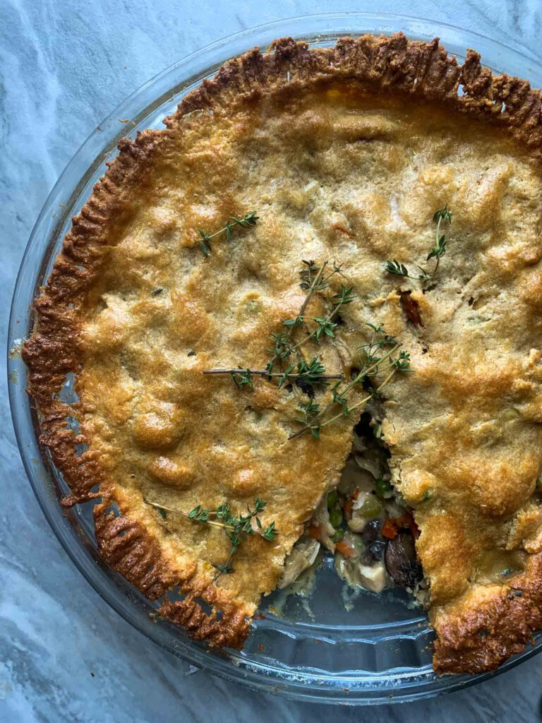 This is a healthy chicken pot pie. There is a brown flaky crust in a circle pie pan, topped with pieces of fresh thyme. There is a piece of pie cut out and you can see the vegetable and chicken filling falling out.