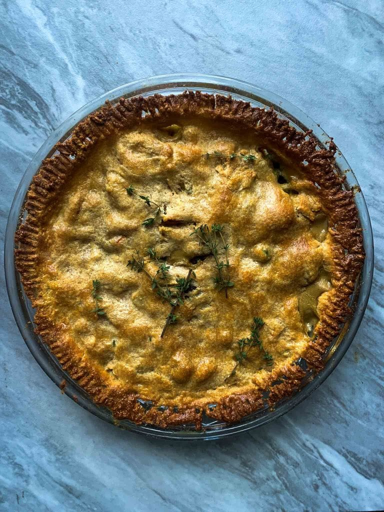 This is a healthy chicken pot pie. There is a brown flaky crust in a circle pie pan, topped with pieces of fresh thyme.