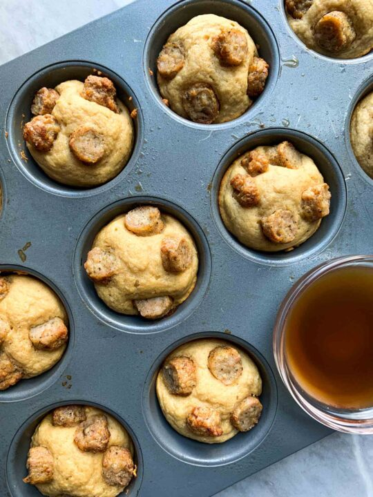 These are pancake sausage bites. There is a muffin tin filled with little pancake muffins with pieces of sausage on top. There is a small bowl of syrup as well.