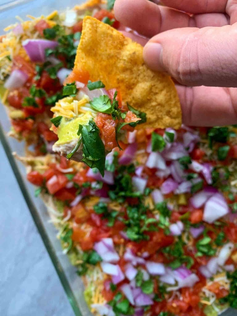 This is a pin filled with healthy 7 layer dip. There are red onions, red tomatoes, cilantro, cheese, and guacamole you can see layered. There is a hand holding up one of the tortilla chips as well.