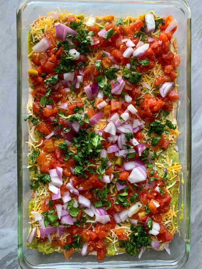 This is a pin filled with healthy 7 layer dip. There are red onions, red tomatoes, cilantro, cheese, and guacamole you can see layered.